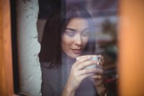 Belle femme prenant une tasse de café dans un café — Photo de stock
