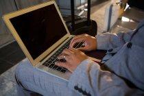Hombre usando el ordenador portátil mientras está sentado en la sala de espera en la terminal del aeropuerto - foto de stock