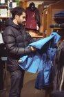 Homem selecionando vestuário em uma loja de roupas — Fotografia de Stock