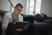 Man using digital tablet while his friend sleeping in background on sofa — Stock Photo