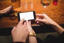 Крупный план пары с помощью мобильного телефона на стойке бара — стоковое фото