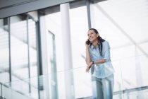 Деловая женщина разговаривает по мобильному телефону в офисном здании — стоковое фото