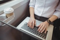 Mid-section of businesswoman using laptop while travelling — Stock Photo