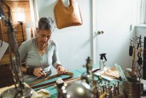 Attentive craftswoman cutting leather in workshop — Stock Photo