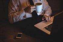 Sección media del hombre de negocios que usa el ordenador portátil mientras toma café en casa - foto de stock