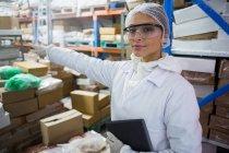 Porträt einer Technikerin, die auf Fleischfabrik zeigt — Stockfoto