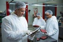 Techniker nutzen digitales Tablet in Fleischfabrik — Stockfoto