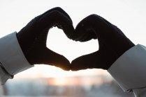 Close up de mão fazendo uma forma de coração contra o nascer do sol — Fotografia de Stock