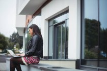 Женщина с ноутбуком возле офисного здания — стоковое фото