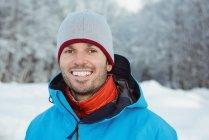 Портрет улыбающегося человека, стоящего на снежном ландшафте — стоковое фото