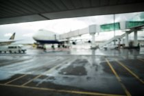 Airplane parked on runway at airport terminal — Stock Photo