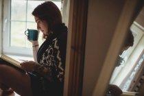 Женщина пьет кофе и читает книгу, сидя дома на подоконнике. — стоковое фото