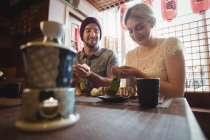 Couple having sake while eating sushi in restaurant — Stock Photo