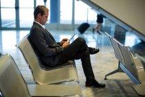 Бизнесмен, использующий цифровой планшет в зоне ожидания терминала аэропорта — стоковое фото