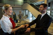 Жіночий персонал вручення багажу бізнесмен в термінал — стокове фото