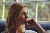 Femme réfléchie regardant par la fenêtre dans le salon à la maison — Photo de stock