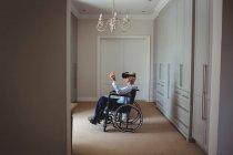 Homme âgé assis sur fauteuil roulant et utilisant un casque de réalité virtuelle à la maison — Photo de stock