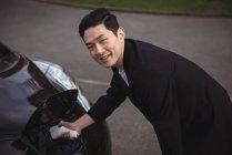 Усміхнений чоловік зарядки машина на електричного автомобіля зарядний — стокове фото