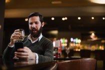 Uomo che beve un bicchiere mentre usa il cellulare nel bar — Foto stock