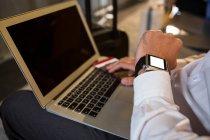 Hombre con el ordenador portátil comprobar el tiempo mientras está sentado en la terminal del aeropuerto - foto de stock
