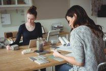 Geschäftsführer schaut sich Steinplatte an, während Kollege im Büro digitales Tablet nutzt — Stockfoto