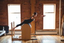 Side view of woman practicing pilates in fitness studio — Stock Photo