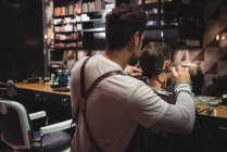 Man getting hair trimmed by hairdresser with scissors in barber shop — Stock Photo