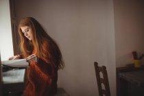 Femme rousse lecture livre à la fenêtre dans le restaurant — Photo de stock