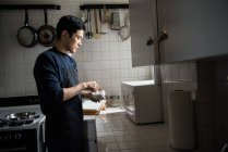 Hombre usando mortero y mortero en la cocina en casa - foto de stock