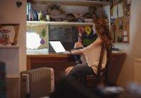 Beautiful woman using laptop at home — Stock Photo
