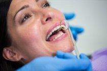 Primo piano del medico che esamina i denti delle pazienti con lo specchio della bocca — Foto stock