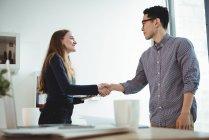 Dirigenti aziendali che si stringono la mano in ufficio — Foto stock