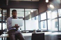 Вдумчивый бизнесмен работает за ноутбуком в офисе — стоковое фото