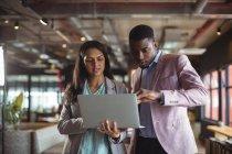 Uomo d'affari e un collega discutono di laptop in ufficio — Foto stock