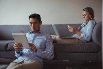 Пара с помощью мобильного телефона, ноутбука и цифрового планшета в гостиной на дому — стоковое фото