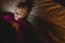 Fille en utilisant une tablette numérique tout en se reposant dans la chambre à coucher à la maison — Photo de stock