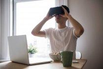 Homem usando fone de ouvido de realidade virtual na sala de estar em casa — Fotografia de Stock
