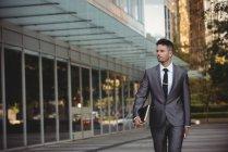 Empresário com um diário andando no campus do escritório — Fotografia de Stock