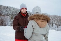 Woman giving gift to smiling man on snow covered mountain — Stock Photo