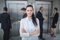 Портрет впевнено бізнес-леді посміхаючись в офісі — стокове фото