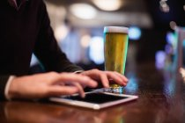 Man using digital tablet with glass of beer on counter in bar — Stock Photo