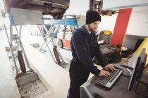 Mechaniker arbeitet in Reparaturwerkstatt am PC — Stockfoto