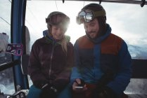 Happy couple using mobile phone while sitting in overhead cable car against sky during winter — Stock Photo