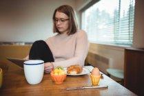 Femme utilisant une tablette numérique tout en prenant le petit déjeuner dans le salon à la maison — Photo de stock