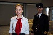 Ritratto di pilota felice e hostess aerea in piedi nel terminal dell'aeroporto — Foto stock