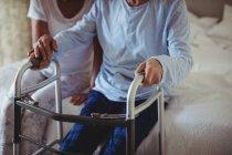 Старшая женщина помогает старшему мужчине гулять с Уокером дома — стоковое фото