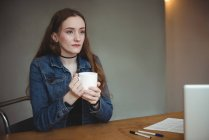 Thoughtful woman having cup of coffee in office — Stock Photo