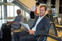 Portrait of businessman reading newspaper in waiting area at airport — Stock Photo