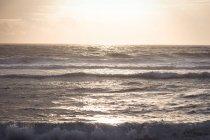 Vagues et réflexion de la lumière du soleil sur la mer au crépuscule — Photo de stock