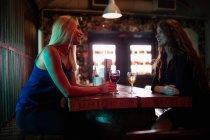 Женщины общаются за бокалом вина в баре — стоковое фото